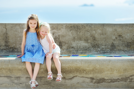 baby love: Two adorable little sisters laughing and hugging each other on warm and sunny summer day in italian town