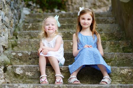 Zwei entzückende kleine Schwestern lachen und umarmen sich gegenseitig an warmen und sonnigen Sommertag in der italienischen Stadt Standard-Bild