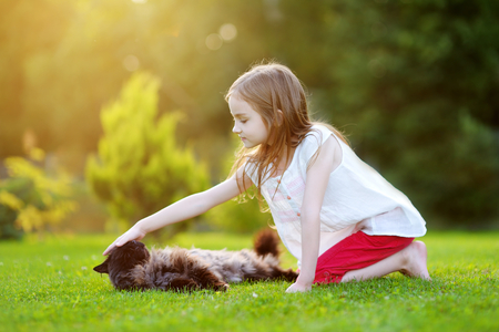 stoking: Cute little girl petting a giant black cat outdoors Stock Photo