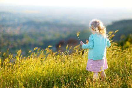 infancia: Adorable niña que se divierte en un prado en cálido y soleado día de verano