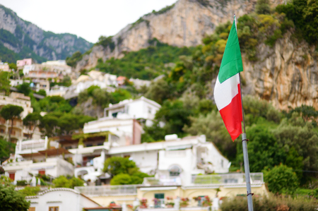 positano: Italian flag over beautiful town of Positano at famous Amalfi coast, Italy Stock Photo