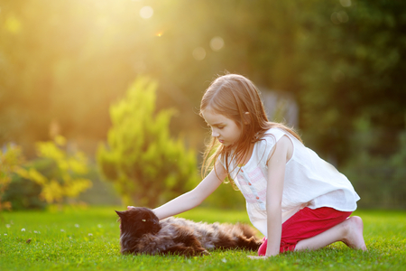 Cute little girl petting a giant black cat outdoors Stock Photo