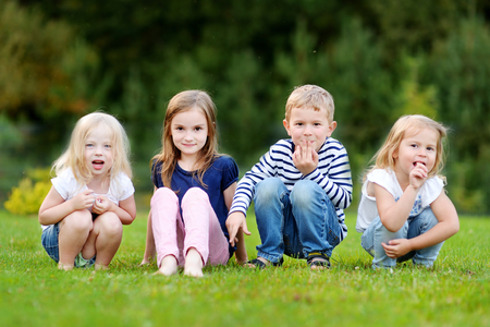 child laughing: Four adorable little kids outdoors at warm summer day