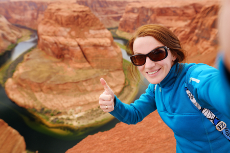 Young tourist taking a photo of herself by famous Horseshoe Bend, Arizona, USA Stock Photo