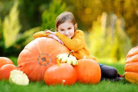huge: Adorable little girl having fun on a pumpkin patch on beautiful autumn day outdoors Stock Photo