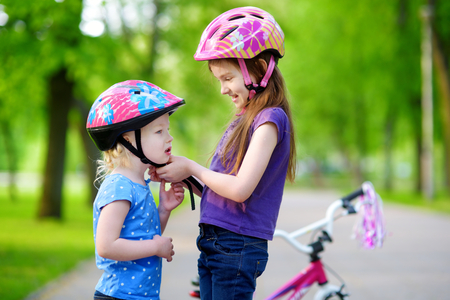 helmet seat: Adorable girl helping her little sister to put a bicycle helmet on Stock Photo