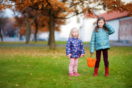 crafting: Little girls gathering acorns for crafting and playing on beautiful autumn day outdoors Stock Photo