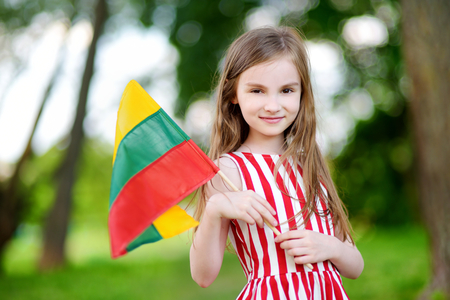 statehood: Cute little girl holding tricolor Lithuanian flag on Lithuanian Statehood Day Stock Photo