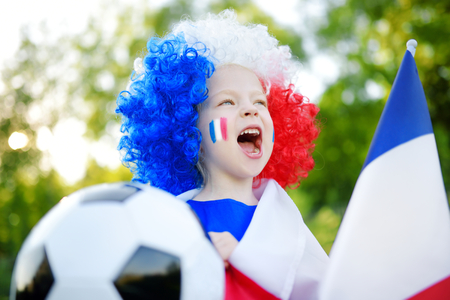 Funny little girl supporting and cheering her national football team during soccer championship