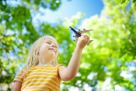 air travel: Adorable little girl playing with small toy airplane outdoors on warm and sunny summer day