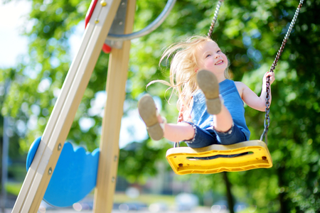 Cute little girl having fun on a playground outdoors in summer Banque d'images