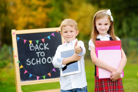 early childhood: Two adorable little schoolkids feeling very excited about going back to school