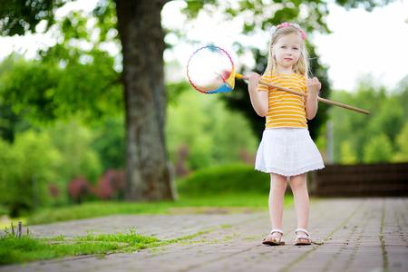 butterfly net: Cute little girl catching butterflies with a scoop-net on summer day