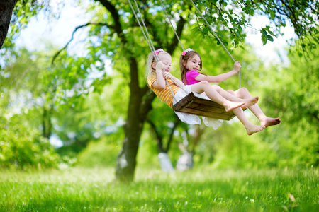 family and friends: Two cute little sisters having fun on a swing together in beautiful summer garden on warm and sunny day outdoors