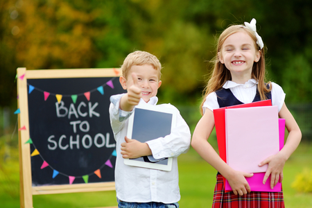 schoolkids: Two adorable little schoolkids feeling very excited about going back to school