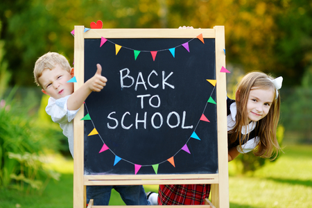 school girl uniform: Two adorable little schoolkids feeling very excited about going back to school