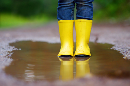 Child wearing rain boots standing in a puddle on warm summer day