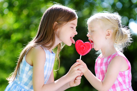 Two cute little sisters eating huge heart-shaped lollipop outdoors on beautiful summer day Stock Photo