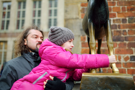 supposed: Little tourist touching famous statue in the center of Bremen known as Bremen Town Musicians, which supposed to bring good luck