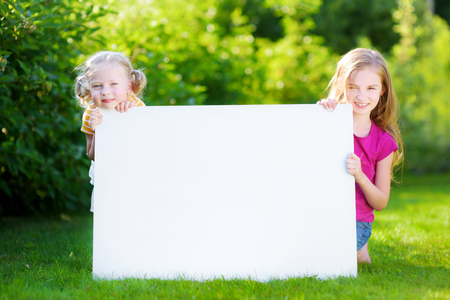 notecard: Two cute little sisters holding big blank whiteboard on warm and sunny summer day outdoors
