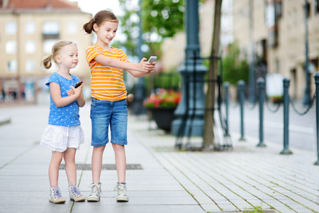 Two cute little sisters playing outdoor mobile game on their smart phones. Kids catching virtual pocket monsters. Modern addictive multiplayer location-based games.