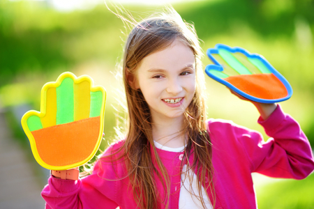 Cute little girl playing a ball catching game with sticky velcro palm pads on beautiful summer day