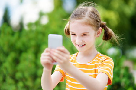 addictive: Cute little girl playing outdoor mobile game on her smart phone. Kid catching virtual pocket monsters. Modern addictive multiplayer location-based games. Stock Photo