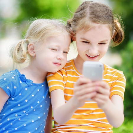 addictive: Two cute little sisters playing outdoor mobile game on their smart phones. Kids catching virtual pocket monsters. Modern addictive multiplayer location-based games.