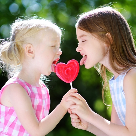 paletas de caramelo: Dos pequeñas hermanas linda que come el lollipop enorme en forma de corazón al aire libre en hermoso día de verano