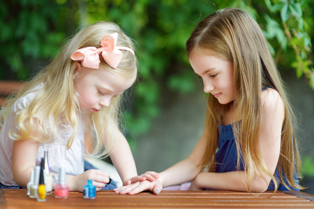 Adorable little girls having fun playing at home with colorful nail polish doing manicure and painting nails to each other Standard-Bild