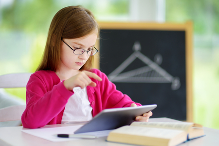 Smart little schoolgirl with digital tablet in a classroom. Child in an elementary school. Education and learning for kids.