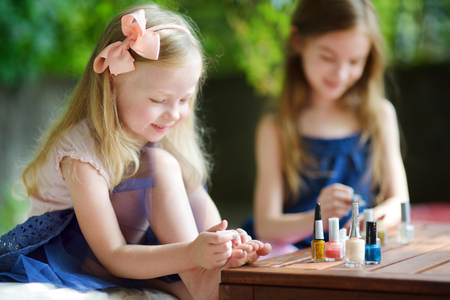 woman foot: Adorable little girls having fun playing at home with colorful nail polish doing manicure and painting nails to each other Stock Photo