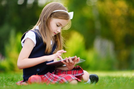 Adorable little girl using computer tablet while sitting on a grass on summer day. Back to school concept.