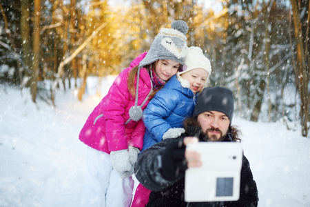 winter vacation: Two cute little sisters taking a selfie with their father on snowy winter day