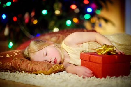 Adorable niña durmiendo bajo el árbol de Navidad junto a una chimenea en Nochebuena Foto de archivo