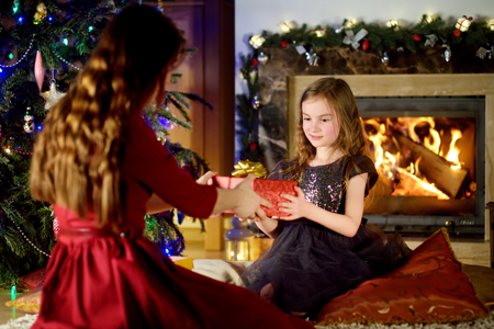 to get warm: Happy little girl getting a Christmas gift from her parent by a fireplace on Christmas eve Stock Photo
