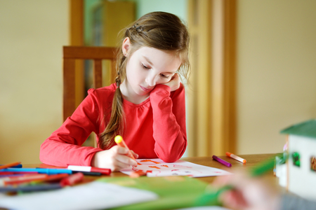 Cute little girl drawing a picture with colorful markers at home Stock Photo