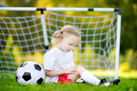 Cute little soccer player hurt her knee while defending a goal in soccer game on sunny summer day