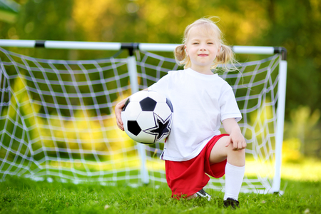 Cute little soccer player having fun playing a soccer game on sunny summer day Stock Photo