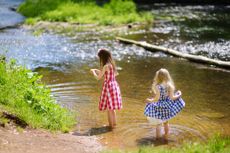 Two cute little girls having fun by a river on warm and sunny summer day Stock Photo