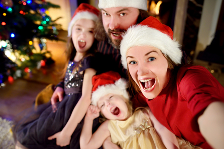 Young happy family of four taking a photo of themselves by a fireplace in a cozy dark living room on Christmas eve