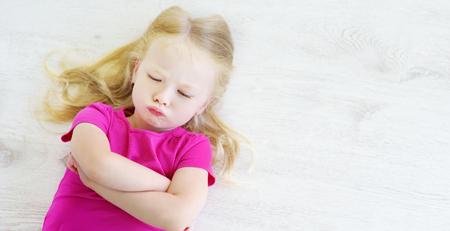 Very angry little girl lying on white wooden floor Stock fotó