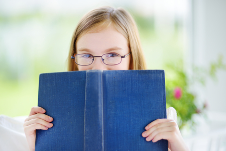 one room school house: Adorable little girl reading a book in white living room on beautiful summer day