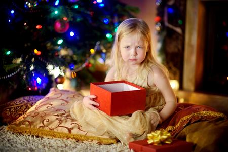 Schattig klein meisje is niet gelukkig met haar kerstcadeau door een open haard in een gezellige donkere woonkamer op kerstavond