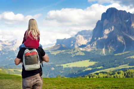 Padre e sua figlia ammirano una vista dell'Alpe di Siusi, il più grande prato alpino d'alta quota in Europa, con splendide montagne rocciose sullo sfondo. Provincia di Bolzano, Italia, Dolomiti. Archivio Fotografico - 64696312