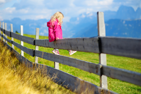 admire: Cute little girl sitting on wooden fence admiring beautiful landscape in Dolomites mountain range, South Tyrol province of Italy Stock Photo