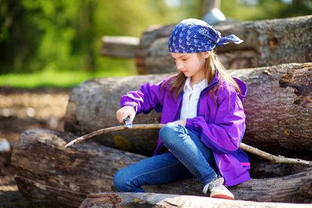Schattig klein meisje zittend op een boom logboeken met behulp van een zakmes aan whittle een wandel-stick. Kind met een vleesmes. Stockfoto