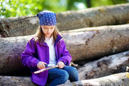 temperino: Cute bambina seduta su tronchi d'albero con un coltello da tasca per Whittle un bastone trekking. Bambino con un coltello.