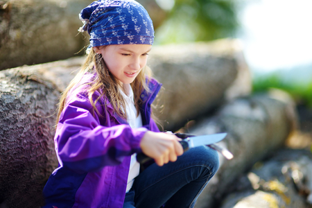 Cute little girl sitting on tree logs using a pocket knife to whittle a hiking stick. Child using a carving knife. Stock Photo