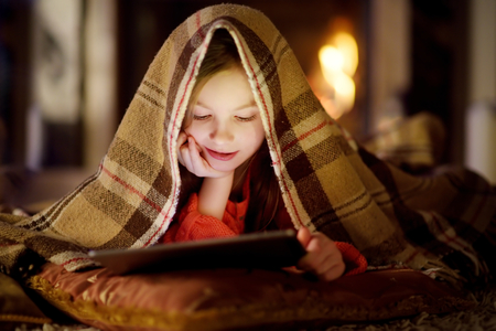 Adorable little girl using a tablet pc by a fireplace on warm Christmas evening